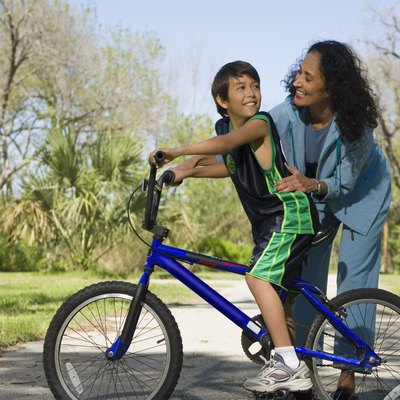 Hispanic mother smiling at son on bicycle