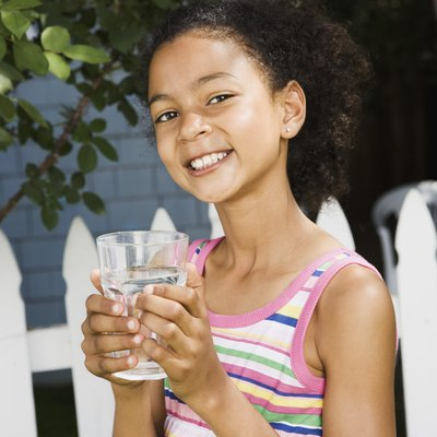 Smiling girl holding water glass