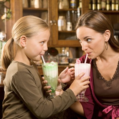 Mother and daughter drinking milkshakes