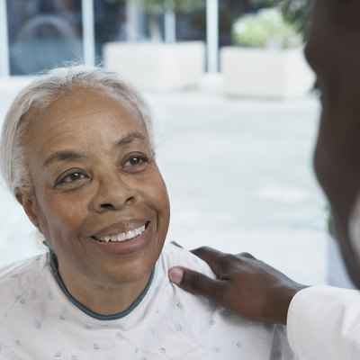 Senior African woman smiling at African doctor in hospital
