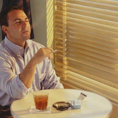 Man smoking, drinking in bar at table