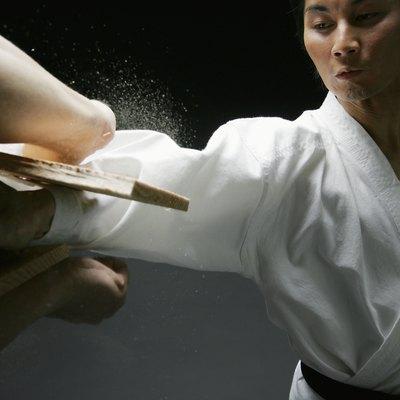 Player of karate, breaking plank