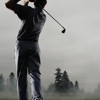 Man playing golf, rear view