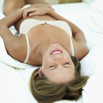 Close-up of a woman lying on a bed holding her stomach in pain