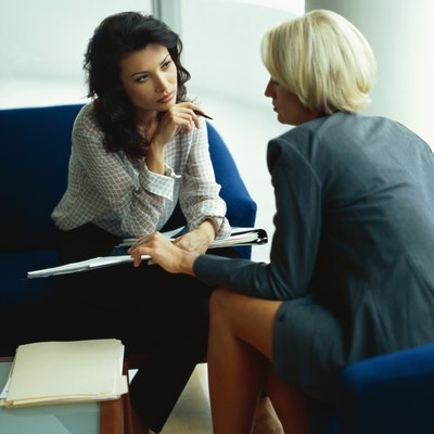 side profile of two businesswomen sitting in an office and talking