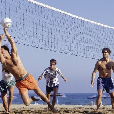 Group of young people playing volleyball on beach