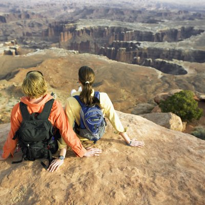 Young couple with backpacks sitting on rock