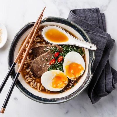 Miso ramen Asian noodles with beef and egg in bowl on white marble background.