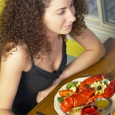 High angle view of a young woman sitting in a restaurant eating lobster