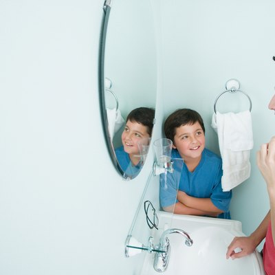 Boy watching brother shave in bathroom