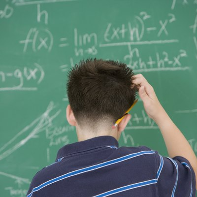 Hispanic boy scratching head in front of blackboard