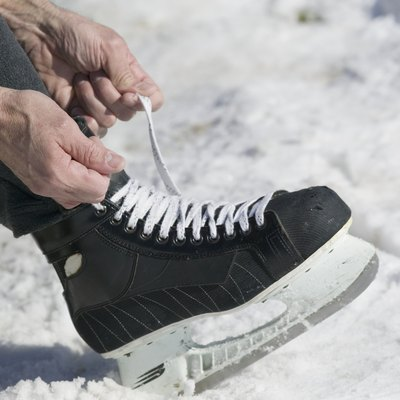 Close up of man lacing ice skate