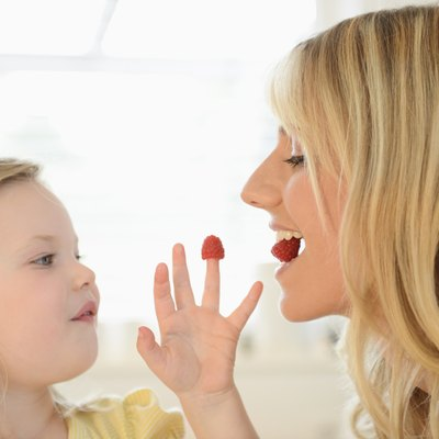 Girl feeding mother with raspberries from her fingers