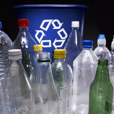 Assorted bottles and trash bin with recycle sign