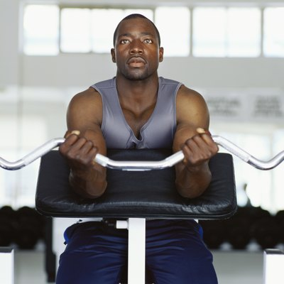 Mid adult man exercising in the gym with weights