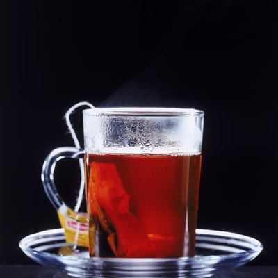 Tea cup with tea bag on black background