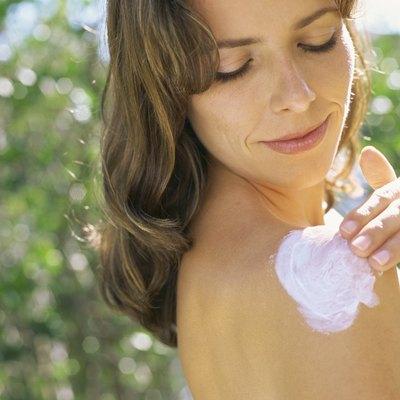 Portrait of a mid adult woman moisturizing her shoulder