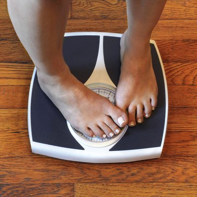 Woman on scale unhappy with her weight