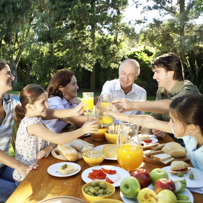 Family, including children (7-11) sitting at table in garden, toasting with orange juice and smiling