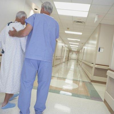 Rear view of male nurse helping senior patient walk in corridor