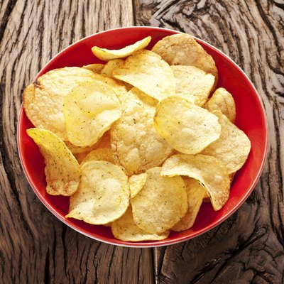 Potato chips in a bowl on old wooden table.