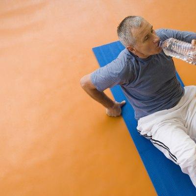 Man sitting on exercise mat, drinking water