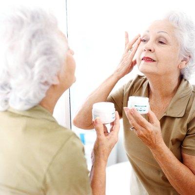 portrait of an elderly woman applying wrinkle cream in the mirror