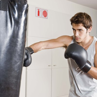 Man boxing on heavy bag at gym
