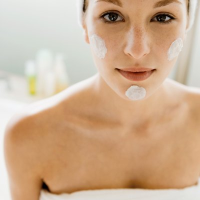 Woman with blots of moisturizer on her face