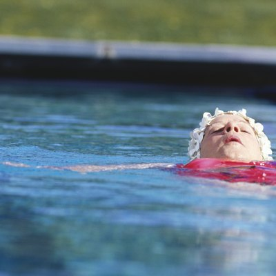 Woman floating on back in outdoor pool, surface view
