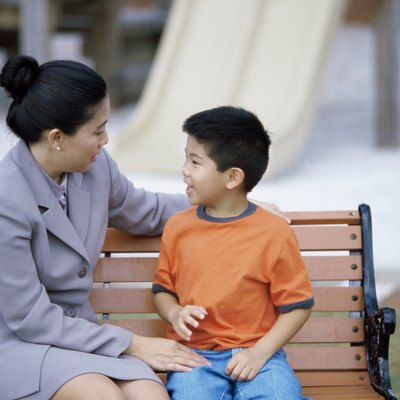 Mother sitting with her son on a park bench