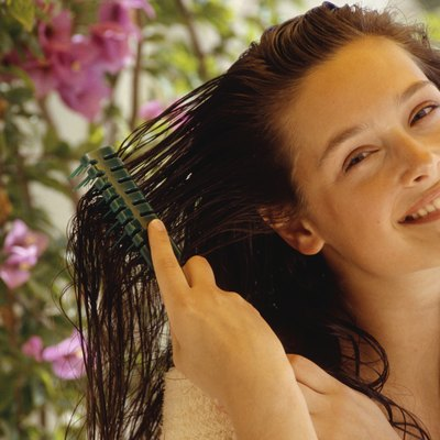 Young woman combing wet hair