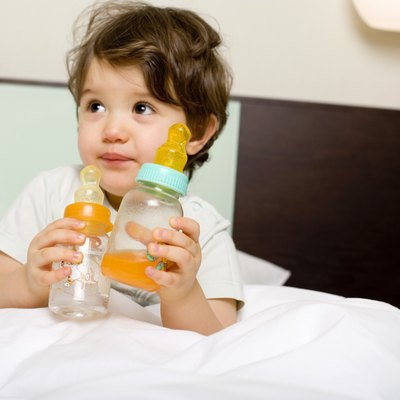 Child with baby bottles in bed