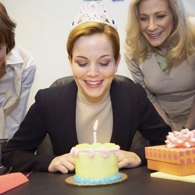 Businesswoman celebrating birthday with colleagues