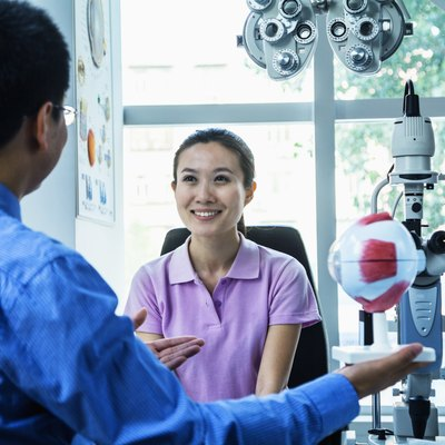 Optometrist discussing with young woman in his clinic
