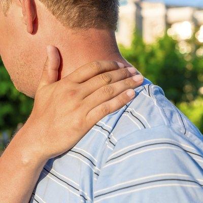 male massaging sore shoulder outdoors