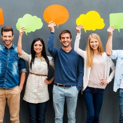 Group of happy young people holding empty speech bubbles and looking at camera while standing against grey background