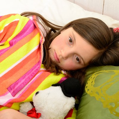 little girl in her bed has a stomachache
