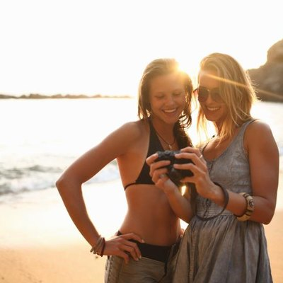 Two girls on beach looking at camera