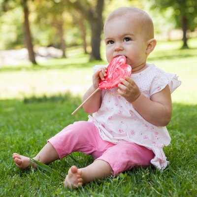 Cute baby with heart shaped lollipop at park
