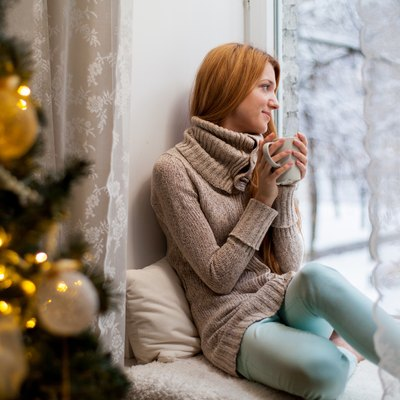 Young woman sitting by the window drinking hot coffee