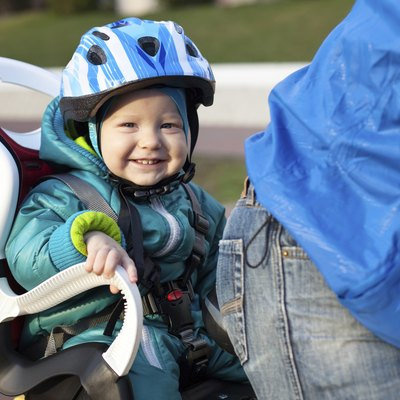 Cheerful little boy in a bike seat