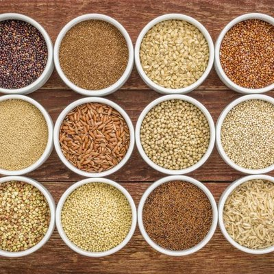 Healthy, gluten-free grains collection (quinoa, brown rice, millet, amaranth, teff, buckwheat, sorghum), top view of small round bowls against rustic wood.