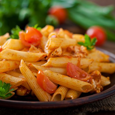 Penne pasta in tomato sauce with chicken, tomatoes