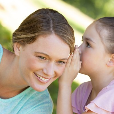 Girl whispering secret into mother's ear at park