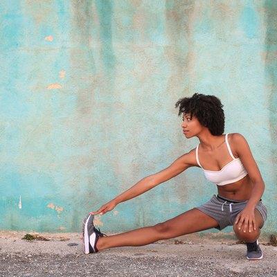 Sportive girl stretching her leg