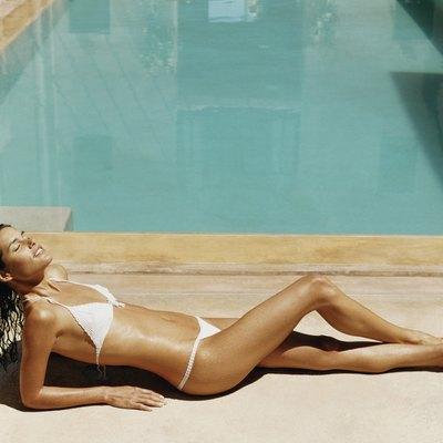 Tanned Woman in a Bikini Sunbathing on the Poolside