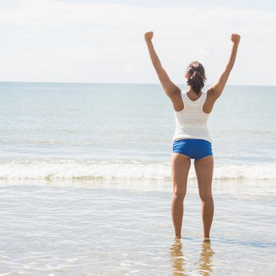 Lovely slim woman standing on beach raising her arms