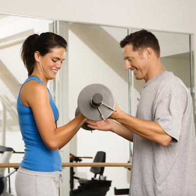 Man and woman lifting weights in gym.