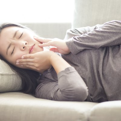 Woman Has Toothache Lying on Sofa